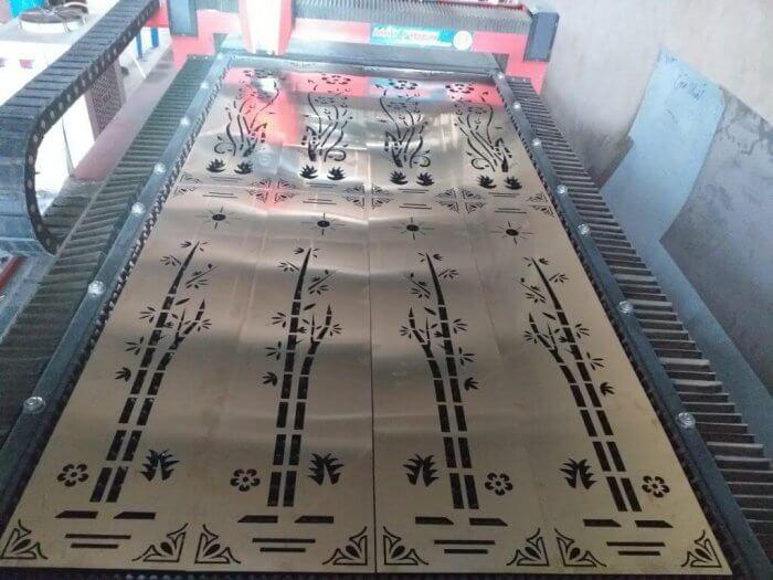 Máy laser đang cắt CNC trên tấm inox mạ vàng